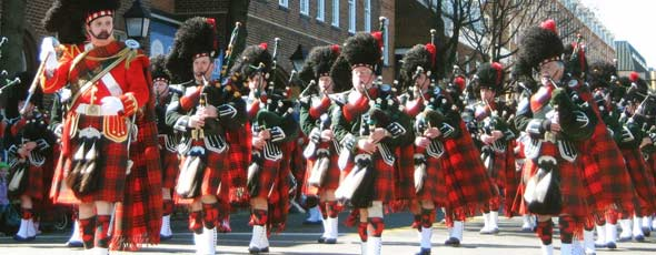 Bagpipers marching in kilts at a festival